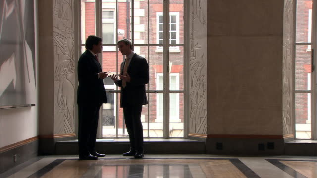 vídeos y material grabado en eventos de stock de ws businessmen having discussion in hallway before walking off together/ london  - pasillo objeto fabricado