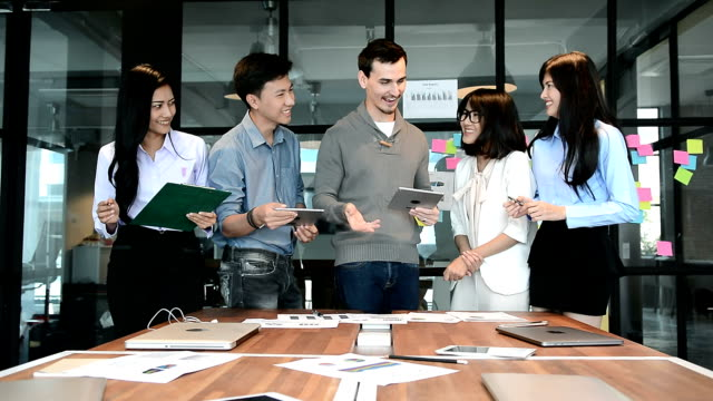 Businessmen holding digital tablet in hand and checking analyze data of growing financial chart of sale with business team in the meeting room at modern office
