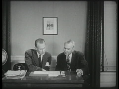 B/W 1941 2 businessmen look at papers on desk then stand + shake hands