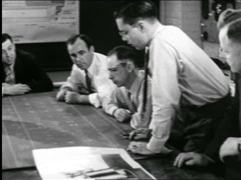 B/W 1944 PAN businessmen looking at blueprints in conference room / industrial