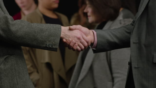 cu businessmen making handshake among crowd. black background - handshake stock videos and b-roll footage