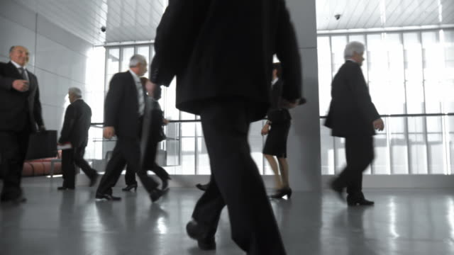 HD DOLLY: Businessmen Meet In Busy Corridor