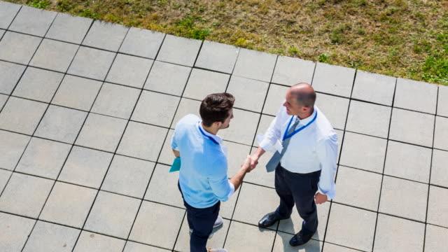 HA businessmen meeting outdoors shaking hands