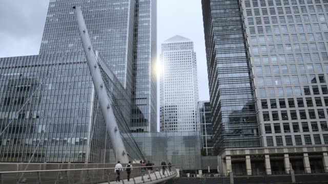 businessmen, people walking on south quay footbridge, canary wharf, london uk - medium group of objects stock videos & royalty-free footage