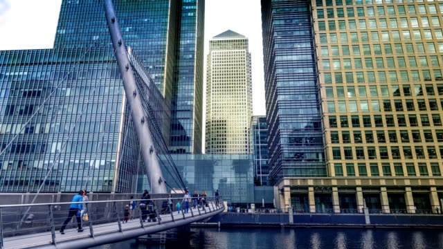 businessmen, people walking on south quay footbridge, canary wharf, london uk - canary wharf stock videos & royalty-free footage