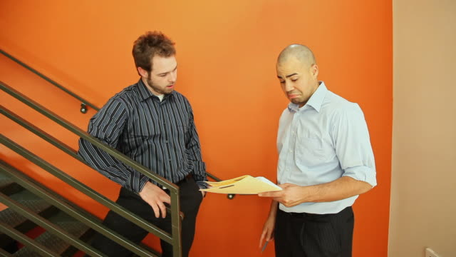 Businessmen reviewing paperwork at office staircase