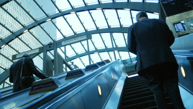 businessmen riding london canary wharf tube station escalator (uhd) - escalator stock videos & royalty-free footage
