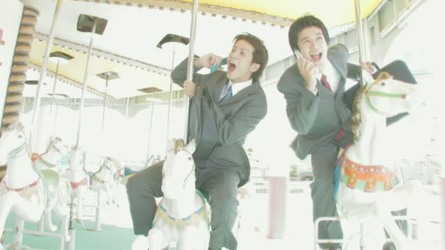 businessmen riding merry-go-round talking on cellular phones - 回転遊具点の映像素材/bロール