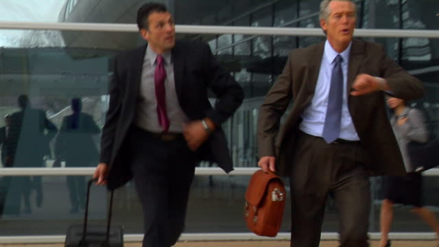 ms pan businessmen running through airport/ pan pilot walking past as woman talks on mobile phone/ virginia beach, virginia - wheeled luggage stock videos and b-roll footage