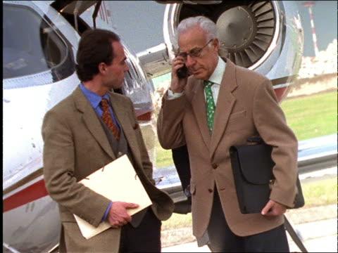vídeos de stock, filmes e b-roll de 2 businessmen shake hands by jet / 1 with cellular phone / slow motion - 1990