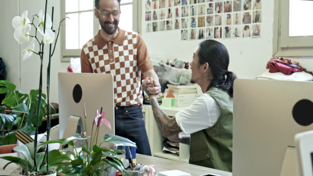 businessmen shaking hands at desk in office - fashion designer stock videos and b-roll footage