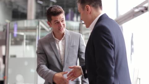 businessmen shaking hands in a corporate office - europäischer abstammung stock-videos und b-roll-filmmaterial