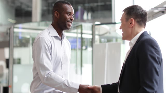 businessmen shaking hands in a corporate office - business relationship stock videos and b-roll footage
