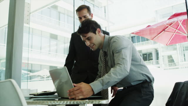ms of businessmen shaking hands then using laptop in office - handshake stock videos and b-roll footage