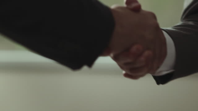 vídeos de stock, filmes e b-roll de businessmen shaking hands. - dando a mão
