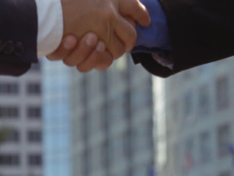 businessmen shaking hands with skyscraper in background - mpeg videoformat bildbanksvideor och videomaterial från bakom kulisserna