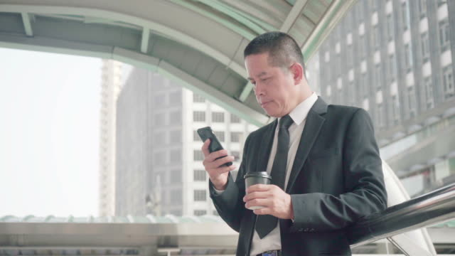 businessmen standing reading messages, talking to family on smartphones during break breaks, lunch and afternoon coffee. - 50 54 years stock videos & royalty-free footage