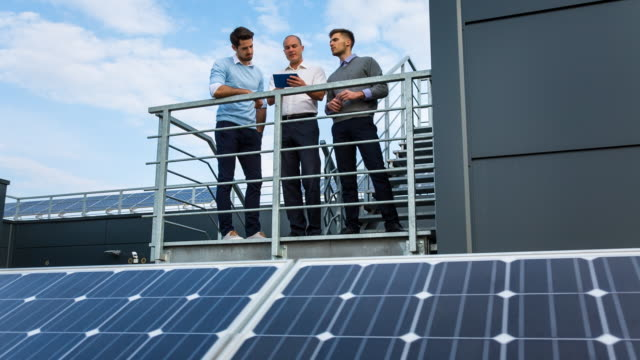 WS businessmen talking between solar panels on rooftop