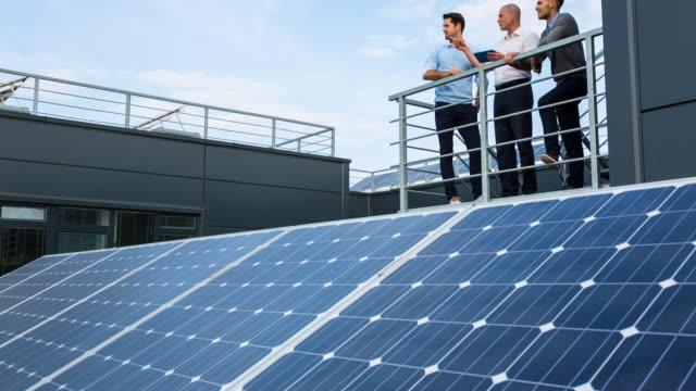 WS businessmen talking between solar panels on rooftop