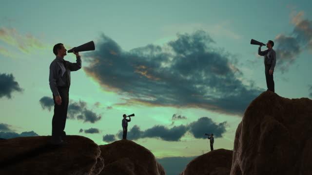 Businessmen talking into a megaphone on a mountain peak/Marbella region, Spain