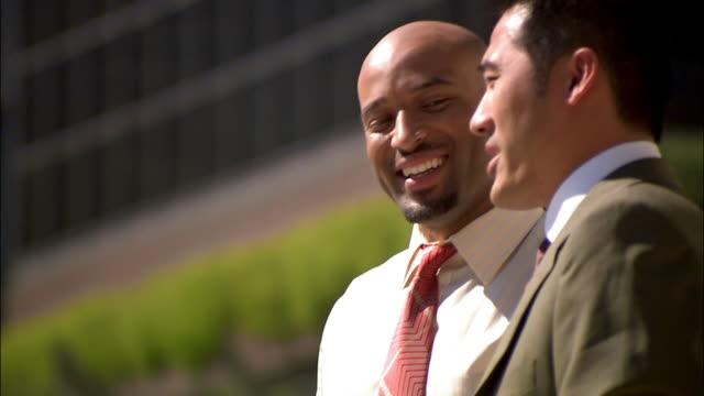 stockvideo's en b-roll-footage met businessmen talking while on break outside - overhemd en stropdas