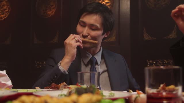 vídeos de stock e filmes b-roll de businessmen toasting glasses and smoking sigars in chinese restaurant - vestuário de trabalho formal