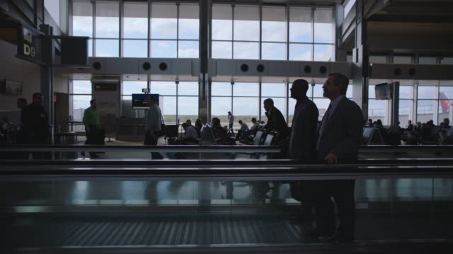 SLO MO. Businessmen travel along moving walkway through airport termial.