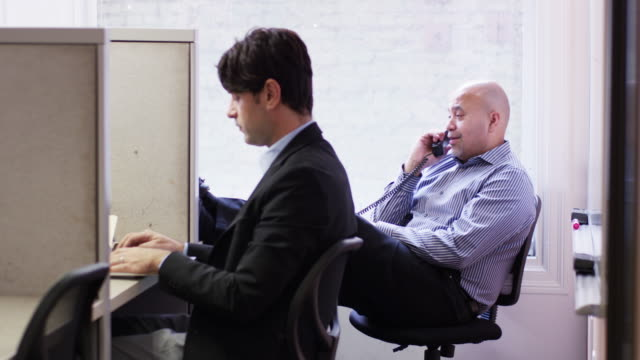 Businessmen using laptop and telephone at office cubicles