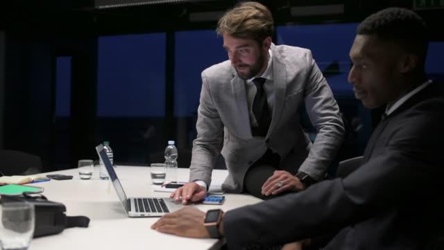vidéos et rushes de businessmen using laptop - costume complet