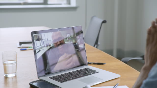 businessmen video chatting on laptop in startup office - voip stock-videos und b-roll-filmmaterial