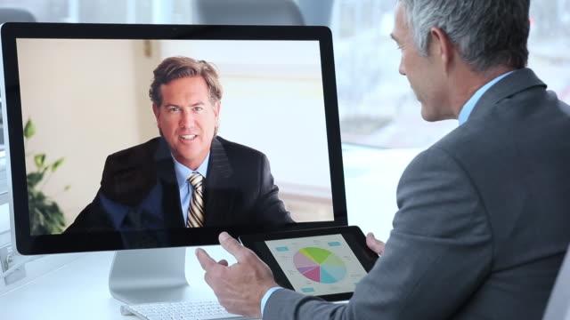vídeos de stock e filmes b-roll de cu businessmen video conferencing in corporate office, discussing financial information / virginia beach, virginia, united states - duas pessoas