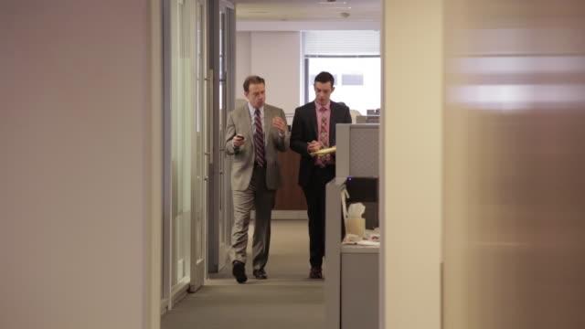 vidéos et rushes de businessmen walk and talk in office hallway - costume complet