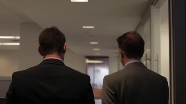 vidéos et rushes de businessmen walk and talk in office hallway - usa mid atlantic