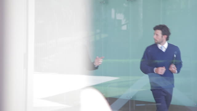 vidéos et rushes de businessmen walking and talking in lobby, viewed through window - cadrage aux genoux