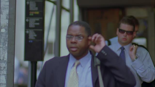 ms pan businessmen walking on city street near wall street subway sign / manhattan, new york, new york, usa - number 3 stock videos & royalty-free footage