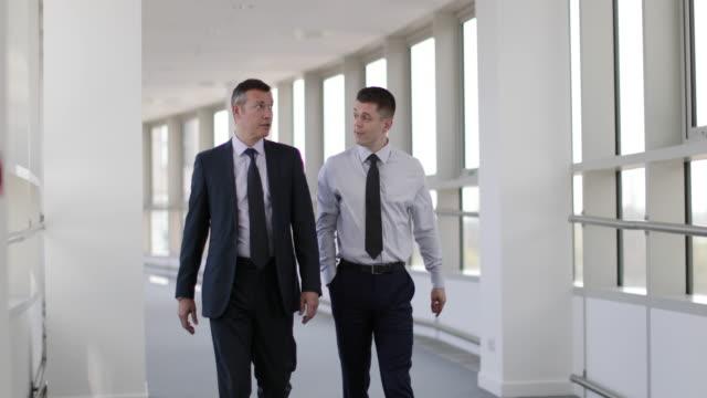 Businessmen walking through office having a meeting