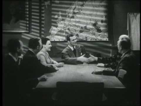 B/W 1950 businessmen + woman talk + shake hands at table in conference room