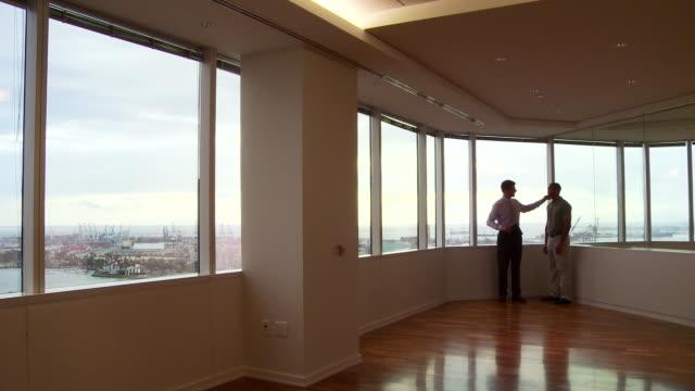 vídeos y material grabado en eventos de stock de businessmen working by office window overlooking city - camisa de polo