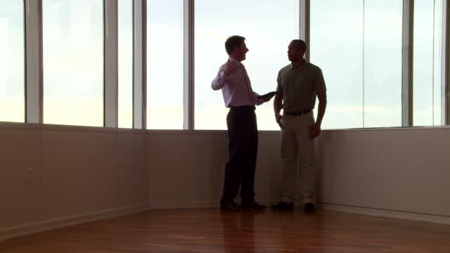 vídeos y material grabado en eventos de stock de businessmen working by office window - camisa de polo