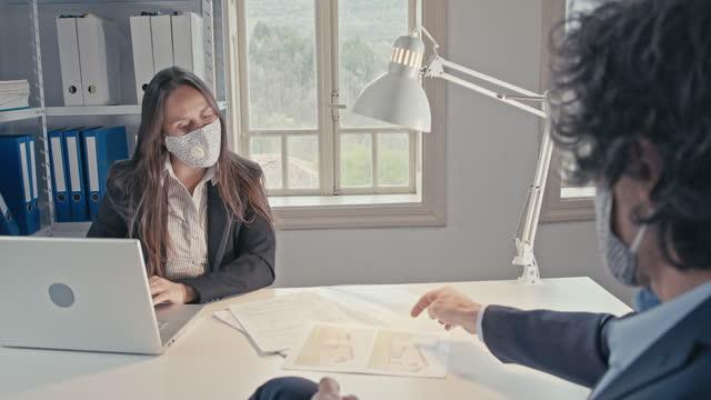 vídeos de stock, filmes e b-roll de empresários no trabalho enquanto covid-19 pandemia, usando máscaras faciais protetoras para achatar a curva. colegas na nova configuração do escritório, co-trabalhando em um projeto, brainstorming, trabalho em equipe. - arquiteto