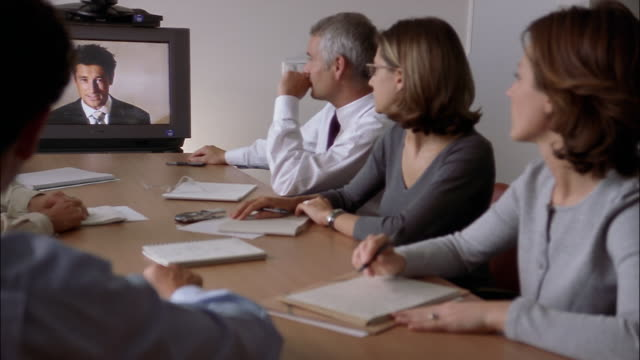 Businesspeople attend a teleconference.