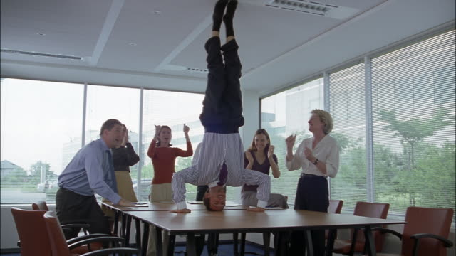 Businesspeople clap as an associate does a headstand on a conference table.