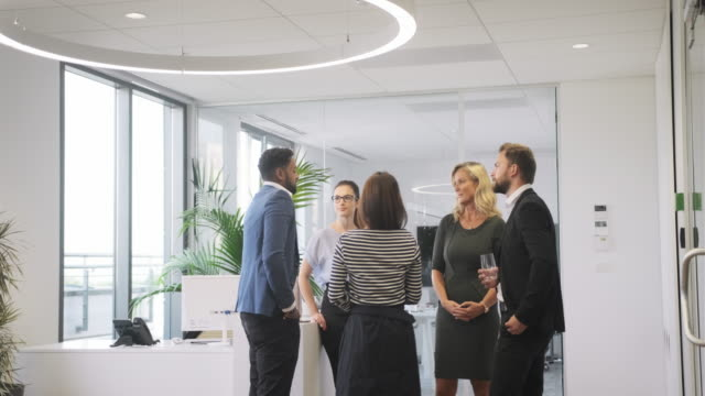 businesspeople exchanging ideas in modern office lobby - mid distance stock videos & royalty-free footage