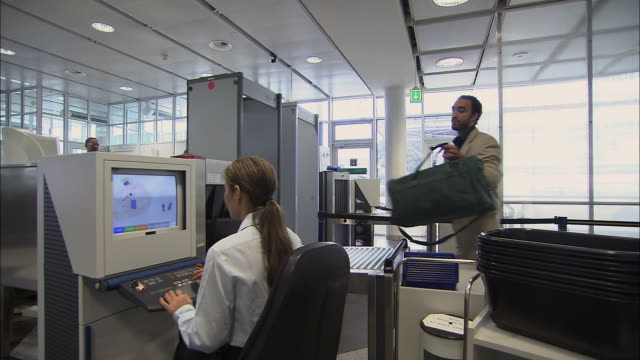 MS Businesspeople going through airport security checkpoint as security worker looks at x-ray monitor/ Munich, Germany