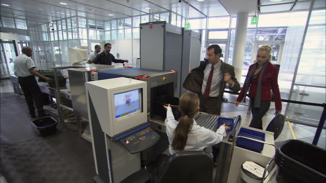 ws pan businesspeople going through airport security checkpoint/ munich, germany - metal detector sicurezza video stock e b–roll