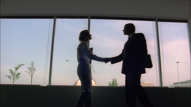 Businesspeople greet each other, shake hands, and talk in front of a large window.
