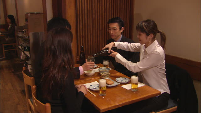 vídeos de stock, filmes e b-roll de ms, businesspeople having meeting in japanese restaurant, woman pouring beer - um dia na vida