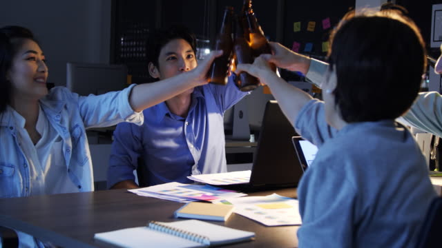 Businesspeople in the office at night working late.Team of young creative developers have brainstorming session at their Meeting Table and drink after work have fun