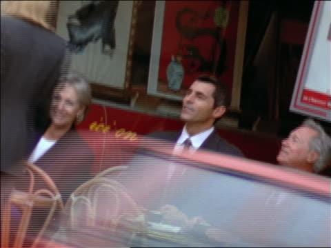 vídeos de stock e filmes b-roll de 4 businesspeople (2 women, 2 senior) meeting at tables outside of cafe / paris, france - sentar se