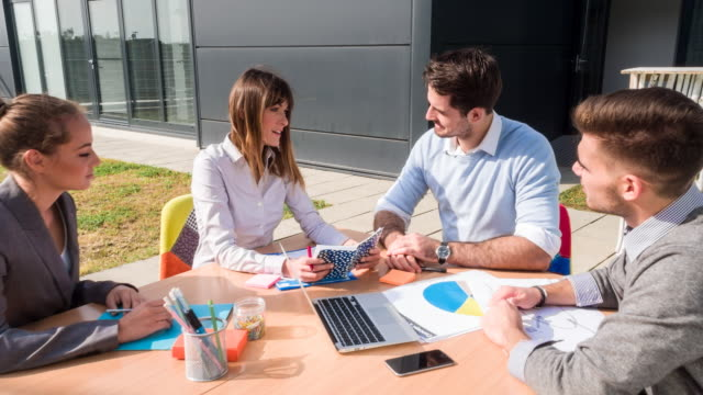 MS businesspeople meeting outdoors around table